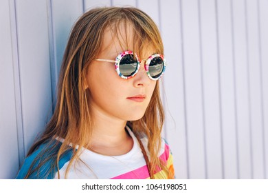 Outdoor close up portrait of adorable little girl wearing modern sunglasses