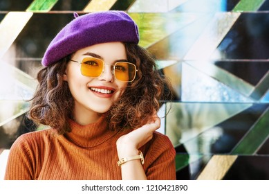 Outdoor close up portrait of beautiful fashionable happy smiling woman wearing purple beret, orange, ochre sunglasses, turtleneck, posing on colorful background, in street. Copy, empty space for text