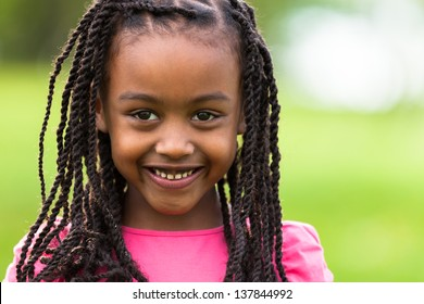 Outdoor close up portrait of a cute young black girl smiling - African people