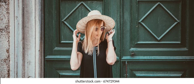 Outdoor close up portrait of model woman in fashionable black dress,and stylish round sunglasses and yellow hat.City lifestyle.Female fashion concept.Retro and vintage filter and colors effect used.