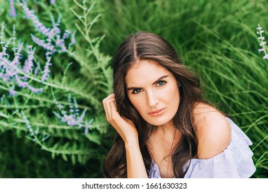 Outdoor close up portrait of pretty young woman with dark hair posing in summer garden with purple flowers