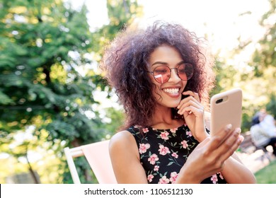 Outdoor close up portrait of smiling black woman using mobile phone and making self portrait . Wearing stylish dress with floral print. Summer park on background.