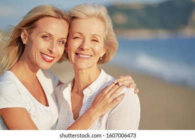 Outdoor close up portrait of smiling happy caucasian senior mother with her adult daughter hugging and looking at the camera on sea beach.