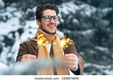 Outdoor close up portrait of young beautiful men with nice hair. Smiling young man having fun with sparklers. . Man enjoy a winter. Dressed in a coat, sweater and scarf .winter concept. Snowfall.