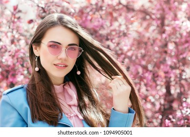 Outdoor close up portrait of young beautiful smiling girl wearing stylish pink color sunglasses, earrings, blue jacket, posing in street near blooming tree. Spring fashion concept. Copy, empty space
