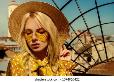 Outdoor close up portrait of young beautiful girl wearing trendy yellow color sunglasses, straw boater hat, polka dot dress posing in street of european city. Summer fashion concept. Copy. empty space
