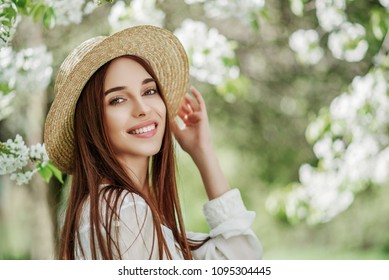 Outdoor close up portrait of young beautiful happy smiling girl with healthy  radiant skin, long natural hair. Model posing in flowering garden. Beauty, health concept. Copy, empty space for text
