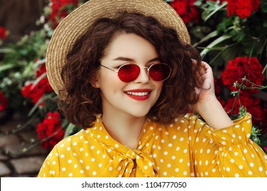 Outdoor close up portrait of young beautiful stylish happy smiling curly girl wearing red narrow oval sunglasses, hat, yellow dress, posing in street with flowers. Summer fashion concept