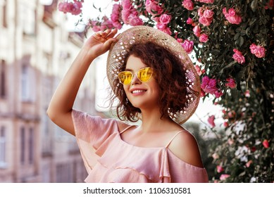 Outdoor close up portrait of young beautiful happy smiling curly girl wearing stylish yellow sunglasses, straw hat, pink top with ruffles. Model posing near blooming roses. Summer fashion concept
