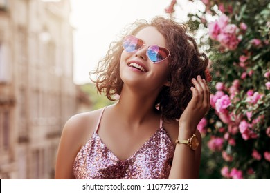 Outdoor close up portrait of young beautiful happy smiling curly girl wearing stylish heart gradient sunglasses, pink sequin blouse, watch. Model posing near blooming roses. Summer fashion concept