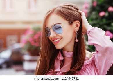 Outdoor close up portrait of young beautiful happy smiling woman wearing blue aviator sunglasses, trendy earrings, posing in street of european city. Copy, empty space for text