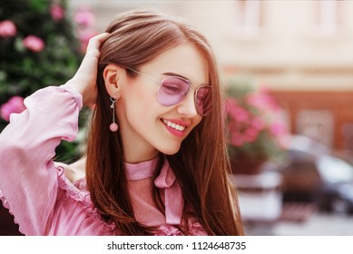 Outdoor close up portrait of young beautiful happy smiling woman wearing pink aviator sunglasses, trendy earrings, posing in street of european city. Copy, empty space for text