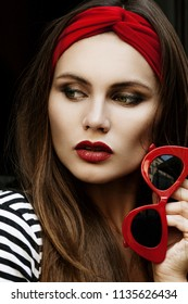 Outdoor close up portrait of young beautiful fashionable woman wearing red headband, holding stylish sunglasses