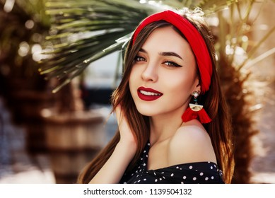 Outdoor close up portrait of young beautiful fashionable happy woman wearing stylish red headband, tassel earrings, polka dot blouse, posing in street under palms. Summer fashion concept. Copy space
