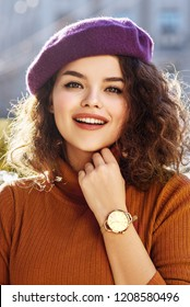 Outdoor close up portrait of young beautiful fashionable happy smiling woman wearing stylish purple beret, orange turtleneck, golden wrist watch, posing in street of european city