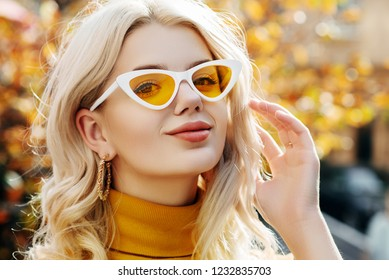 Outdoor close up portrait of young beautiful happy smiling blonde girl wearing white yellow cat eye sunglasses, hoop earrings, turtleneck, posing in street. Natural sunny day light