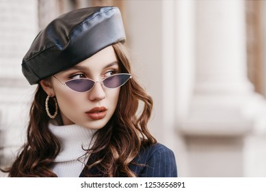 Outdoor close up portrait of young beautiful fashionable woman with long hair wearing trendy sunglasses, hoop earrings, leather beret,  posing in street of european city. Copy, empty space for text