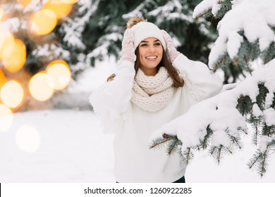 Outdoor close up portrait of young beautiful happy smiling girl wearing white knitted beanie hat, scarf and gloves. Model posing in park with Christmas lights. Winter holidays concept.