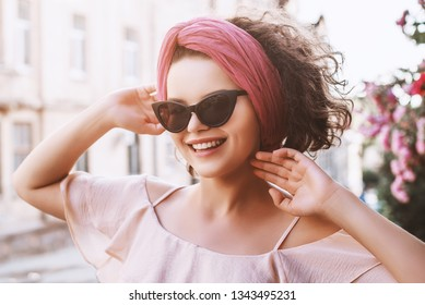 Outdoor close up portrait of young beautiful fashionable happy smiling lady wearing trendy wide pink headband, black cat eye sunglasses, posing in street of European city