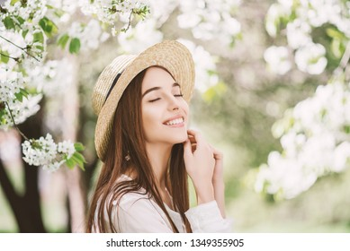 Outdoor close up portrait of young beautiful happy smiling lady with healthy  white teeth, flawless skin, long natural hair, posing in blooming garden, wearing straw hat. Copy, empty space for text