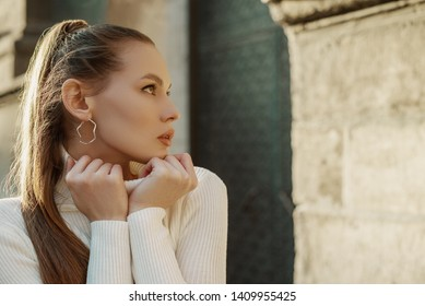 Outdoor close up portrait of young beautiful fashionable woman with long hair wearing trendy hoop earrings, white turtleneck sweater, posing in street of European city. Copy, empty space for text