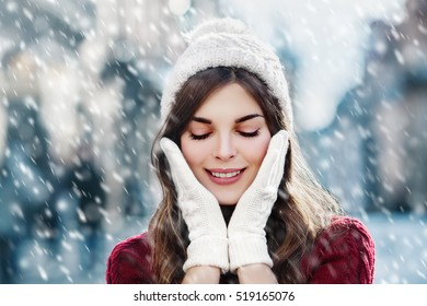 Outdoor close up portrait of  young beautiful happy smiling girl walking on the street. Model closed her eyes and touching face, wearing stylish knitted winter hat and gloves. Magic snowfall effect.