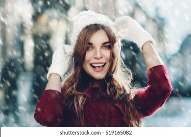 Outdoor close up portrait of young beautiful happy smiling girl, wearing stylish knitted winter hat and gloves. Model expressing joy and looking at camera. Day light. Magic snowfall effect. Toned