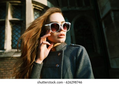 Outdoor close up portrait of young beautiful fashionable woman with long hair wearing stylish light blue sunglasses, grey coat posing on street. Model looking aside. Sunny day. Female fashion concept