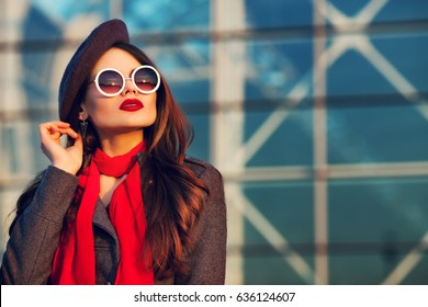 Outdoor close up portrait of young beautiful woman posing on street of european city, looking up. Model wearing stylish beret, sunglasses, scarf. Female fashion concept. Sunset. Copy, empty space