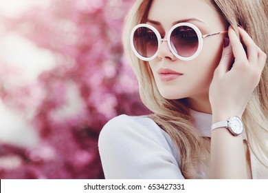 Outdoor close up portrait of young beautiful fashionable girl posing in street. Model wearing stylish white round sunglasses, wrist watch. Female fashion concept.