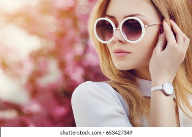 Outdoor close up portrait of young beautiful fashionable girl posing in street. Model wearing stylish white round sunglasses, wrist, hand watch. Female fashion concept.