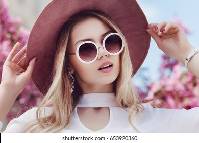 Outdoor close up portrait of young beautiful woman wearing stylish round sunglasses, pink hat, white shirt. Model looking at camera, posing in street, near blooming flowers. Female fashion concept