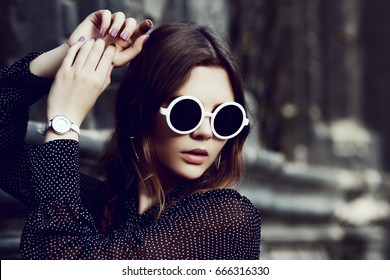 Outdoor close up portrait of young beautiful girl posing in street. Model looking down, wearing stylish white round sunglasses, wrist watch, polka dot blouse. City lifestyle. Female fashion concept