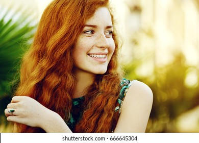 cc470462613 Outdoor close up portrait of young beautiful happy smiling redhead girl  with freckles