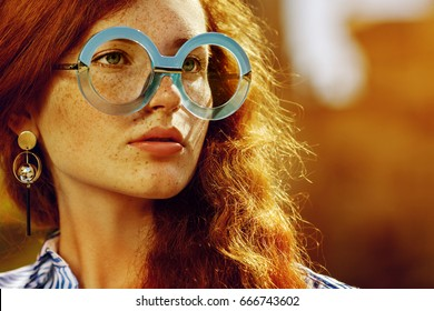 Outdoor close up portrait of young beautiful fashionable redhead girl with freckles, long curly hair. Model wearing trendy round blue glasses, stylish earrings, looking aside. Sunset. Copy space