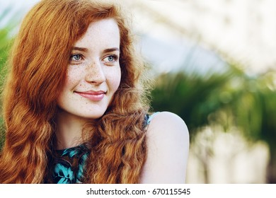 Outdoor close up portrait of young beautiful happy smiling redhead girl with freckles, long curly hair, no makeup. Model posing in street. Female natural beauty, happiness concept. Copy, empty space