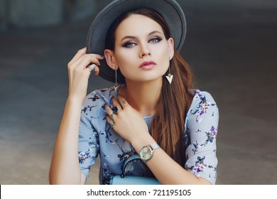 Outdoor close up portrait of young beautiful fashionable woman posing in street, looking at camera. Model wearing stylish gray boater hat, wrist watch, earrings, a lot of rings. Female fashion concept