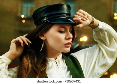 Outdoor close up portrait of young beautiful fashionable woman wearing stylish leather cap posing in street. Model closed eyes. Lights and reflections on background. Female fashion concept