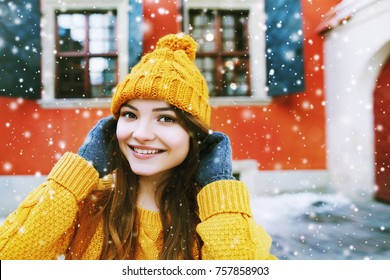 Outdoor close up portrait of young beautiful happy smiling girl posing on street, looking at camera. Model wearing stylish winter yellow hat, sweater, gloves. Snowfall. City lifestyle. Copy space