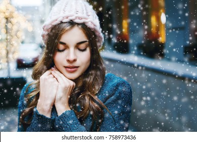 Outdoor close up portrait of young beautiful girl with long hair wearing hat, sweater posing in street of european city.  Christmas, winter holidays concept. Snowfall. Copy, empty space for text