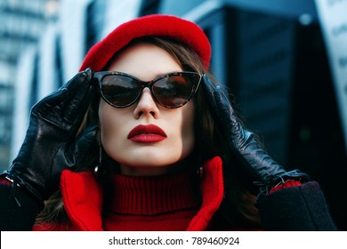 Outdoor close up portrait of young beautiful fashionable woman posing in street. Model wearing red beret, black leather gloves, cat eye sunglasses with leopard print. Female fashion concept.