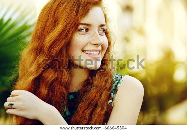Outdoor close-up portret van jonge mooie vrolijke lachende roodharige meisje met sproeten, lang krullend haar, geen make-up. Model poseren op straat. Zomerse zonnige dag. Vrouwelijke natuurlijke schoonheid, geluksconcept