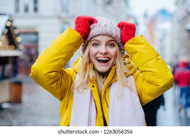 Outdoor close up portrait of young happy smiling girl in knitted hat, red mittens, yellow warm jacket having fun, enjoy snowfall in street of european city. Winter mood, holidays concept. Copy space