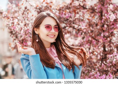 Outdoor close up portrait of  young happy smiling, laughing lady wearing stylish pink cat eye sunglasses, earrings, blue jacket, posing in spring street of European city. Copy, empty space for text