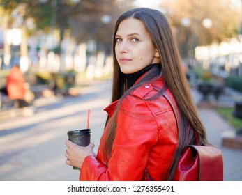 Outdoor close up shot of 20s year stylish brunette woman in red leather coat on lunch break drinking coffee or tea to go. Autumn urban background.