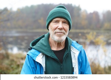 Outdoor close up shot of handsome active elderly male pensioner with gray beard having morning walk in wild nature, posing against misty lake and colorful autumn forest background, looking at camera