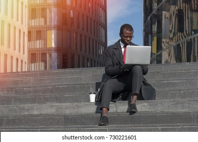 Outdoor closeup of busy African American male doing work, communicating or checking email in short leisure time that he is spending on stairs in street using laptop and drinking takeaway coffee