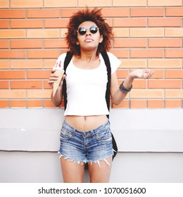 Outdoor closeup fashion portrait of afro american hipster teen crazy girl eating ice cream in summer hot weather in round mirror sunglasses have fun and good mood. Toned style instagram filters