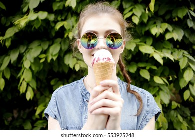 Outdoor closeup fashion portrait of young hipster crazy girl eating ice cream in summer hot weather in round mirror sunglasses have fun and good mood. Toned style instagram filters