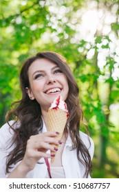 Outdoor closeup portrait of girl eating ice cream in summer